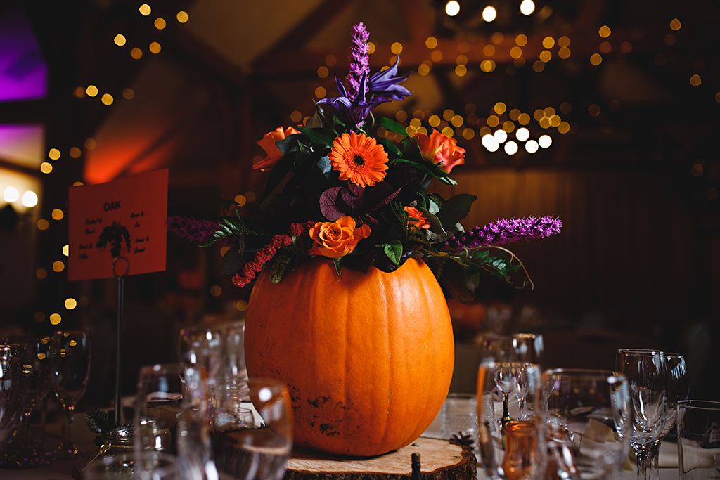 Pumpkins were used as vases for colourful flowers at this barn venue in Cheshire