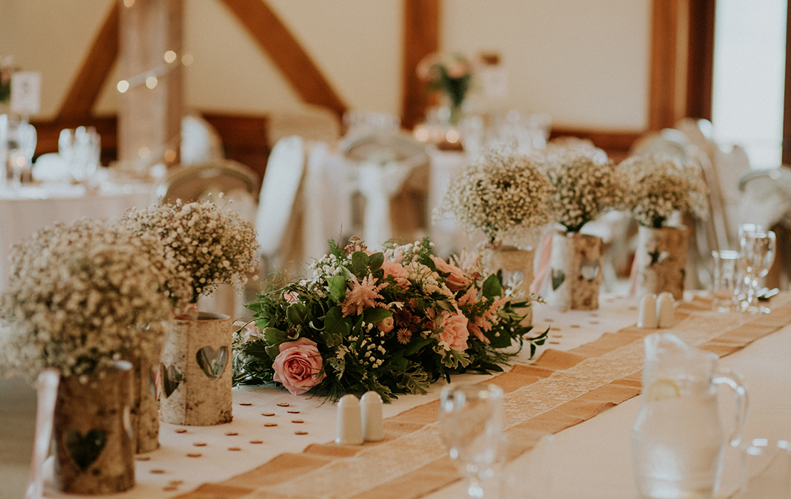 Beautiful spring wedding flowers adorned the top table at this rustic wedding at Sandhole Oak Barn