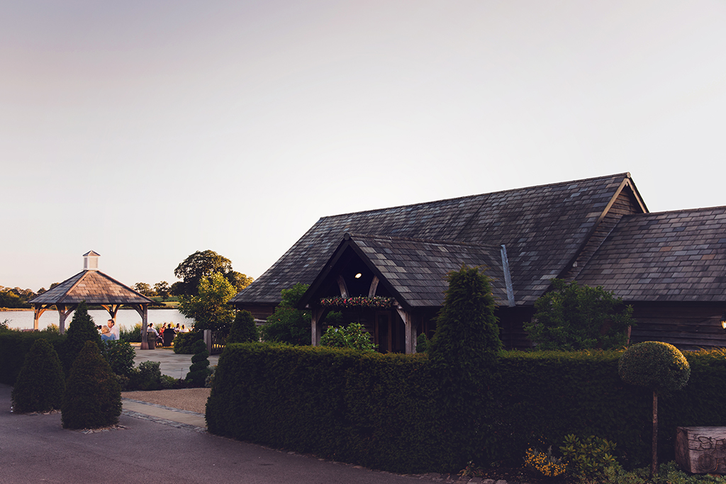 Wedding guests enjoy mingling outside on a summer's evening at this barn wedding venue in Cheshire