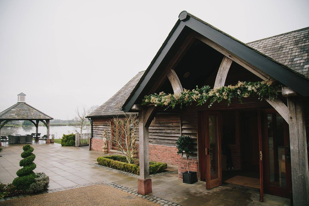 The entrance to the barn was decorated with a festive garland at this winter wedding in Cheshire