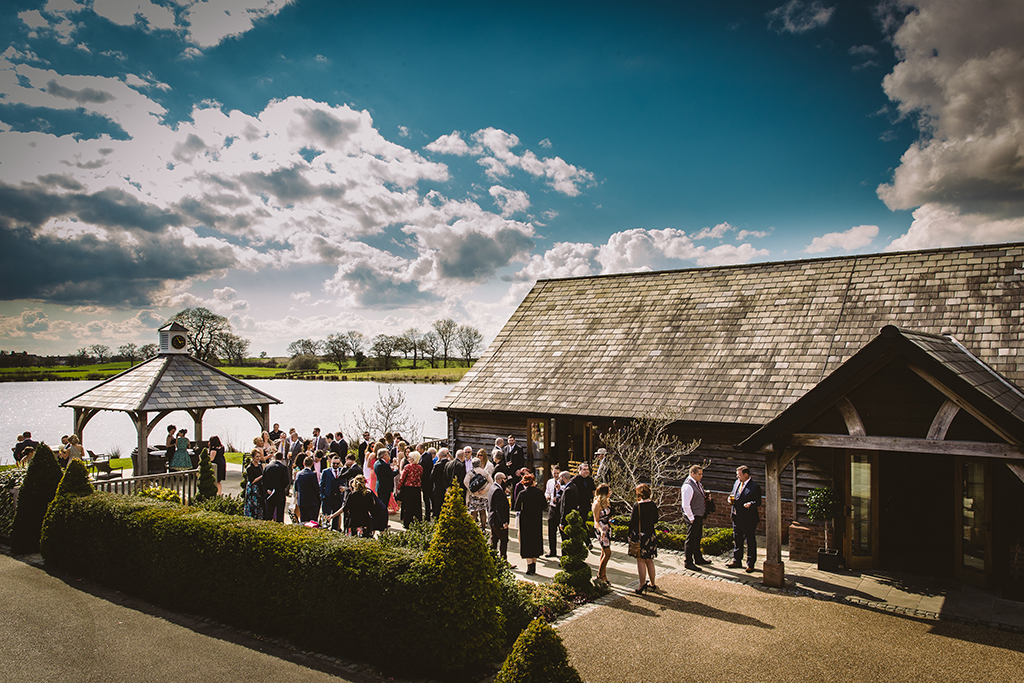 Wedding guests can enjoy the lakeside views as they mingle in the sunshine at this rustic barn wedding venue near Manchester