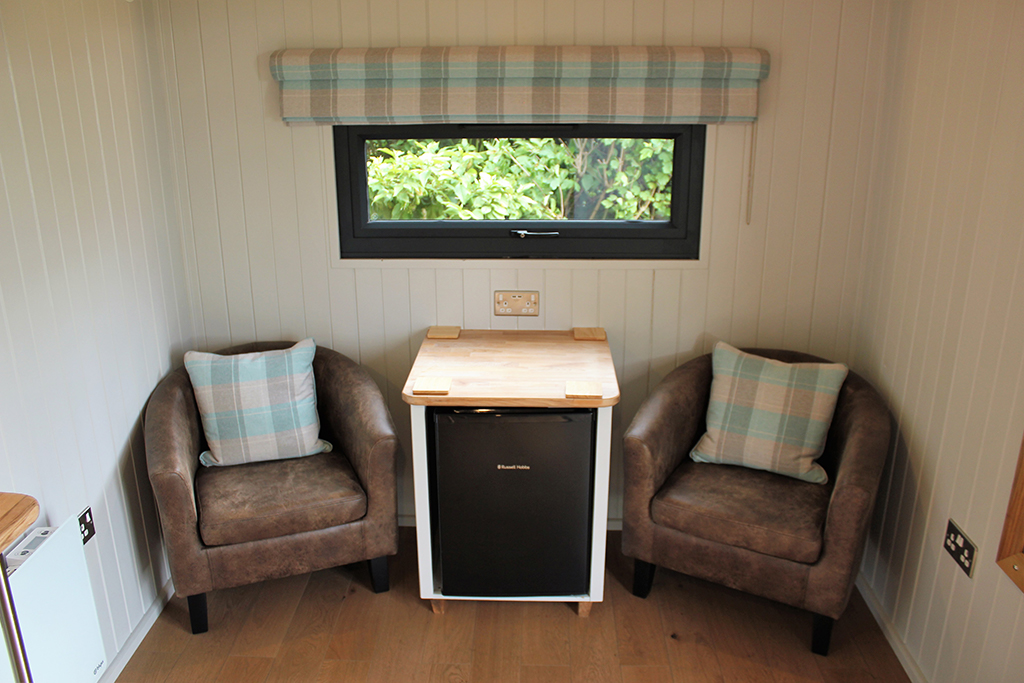 Comfy tub chairs and fridge in the shepherds hut partner preparation room at Sandhole Oak Barn