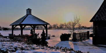 Sandhole Oak Barn looks beautiful in the snow with the sunset in the background