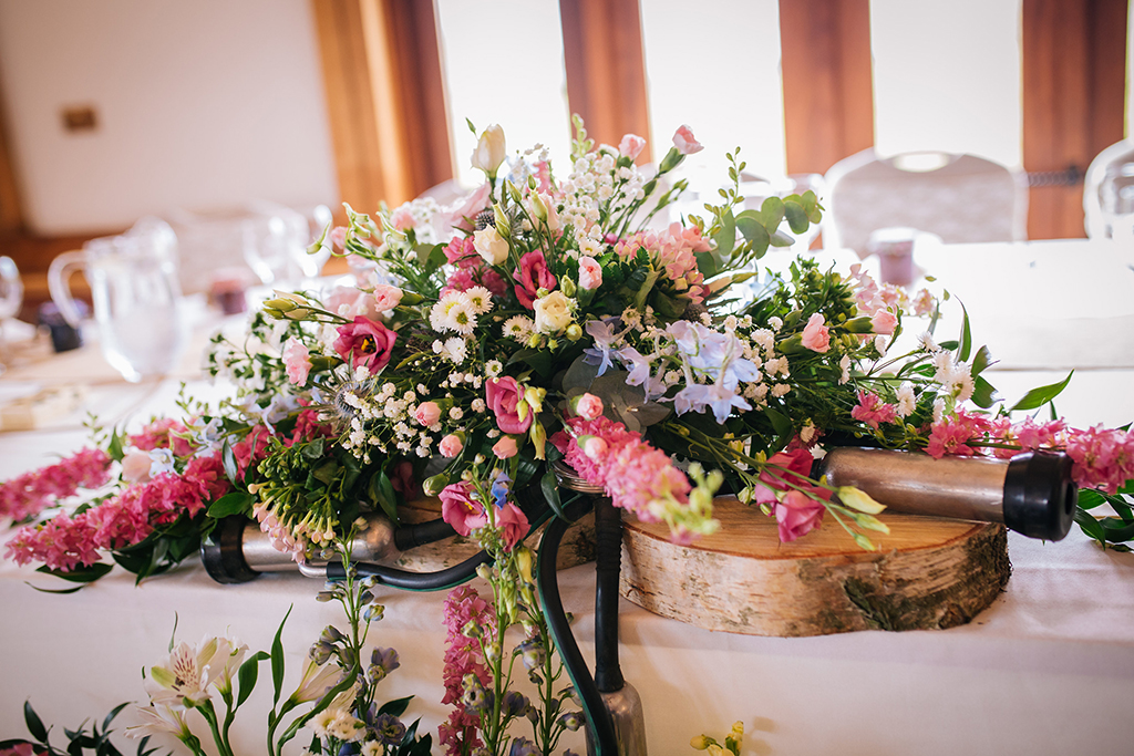 The top table was decorated with a beautiful arrangement of colourful spring flowers and dairy farming parts at Sandhole Oak Barn in Cheshire