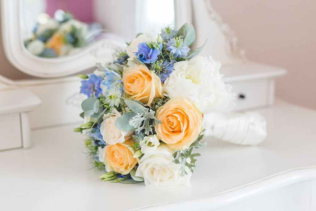 This bouquet is a beautiful mix of blue and peach spring wedding flowers and is perfect for a barn wedding