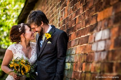 The brides bouquet is made from beautiful sunflowers and the groom has a sunny yellow gerbera buttonhole at this summer barn wedding in Cheshire