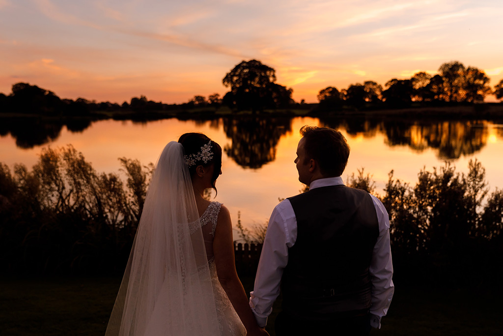 The happy newlyweds enjoy the views of the sun setting over the lake at this rural wedding venue in Cheshire