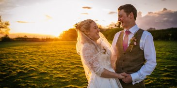 The happy newlyweds have their photo taken in the sunset at this rural wedding venue in Cheshire