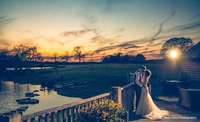 The bride and groom have wedding pictures taken on the verandah in the glorious sunset
