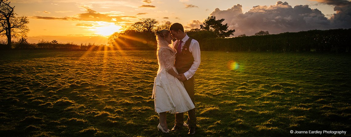 The bride and groom pose for a photo with the stunning sunset in the background at Sandhole Oak Barn near Manchester
