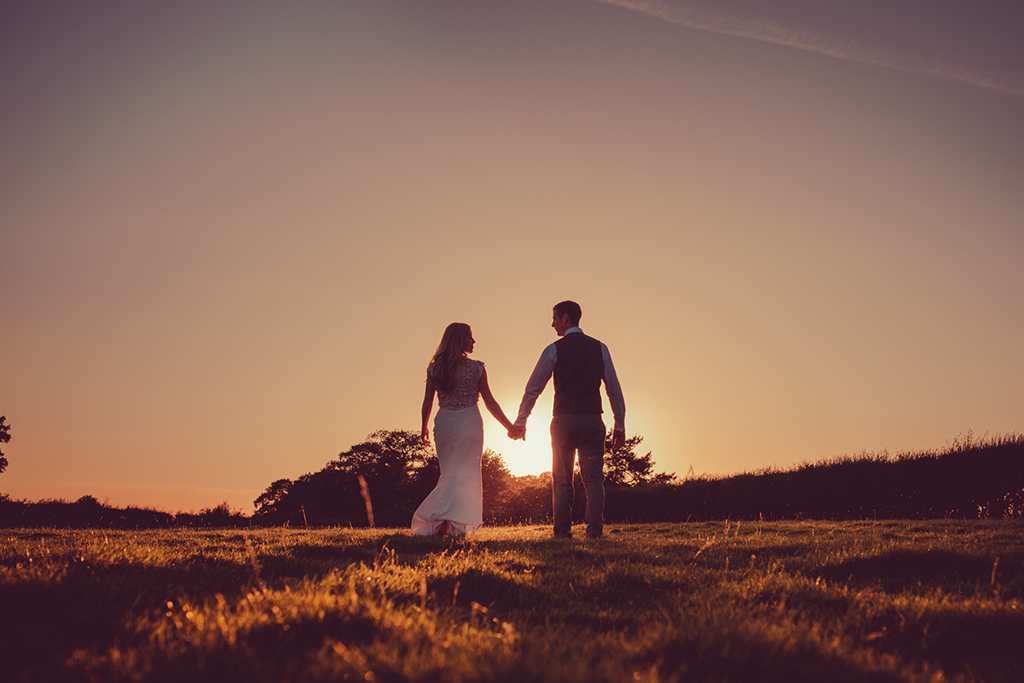 The bride and groom have wedding pictures taken as the sunsets at this beautiful barn venue