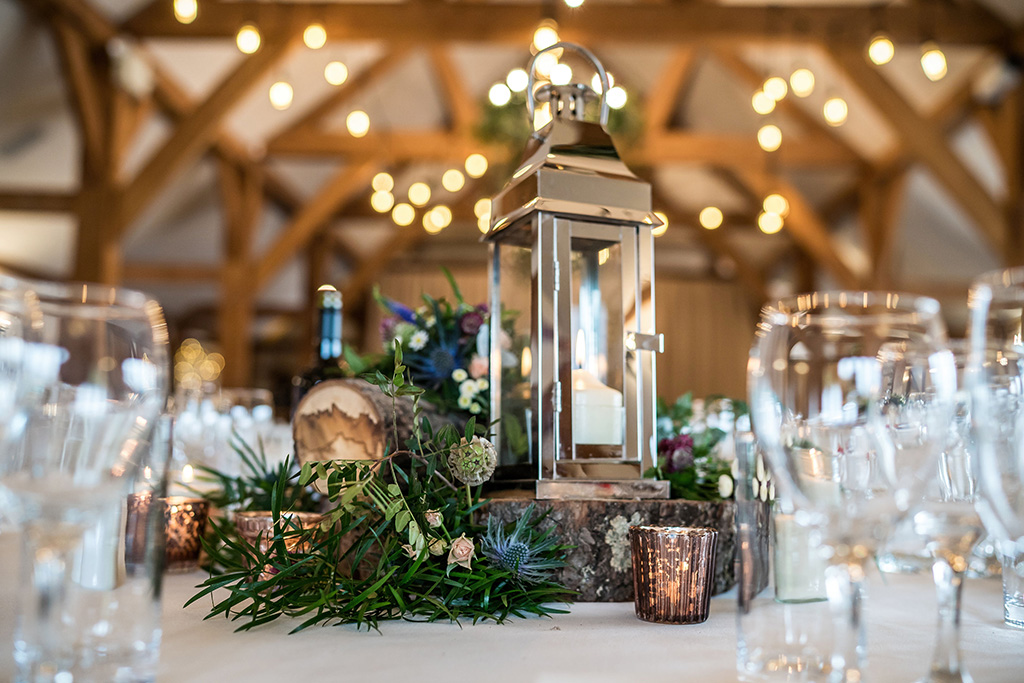 The couple chose lanterns and seasonal flowers displayed on log slices as their table centrepieces at their barn wedding in Cheshire