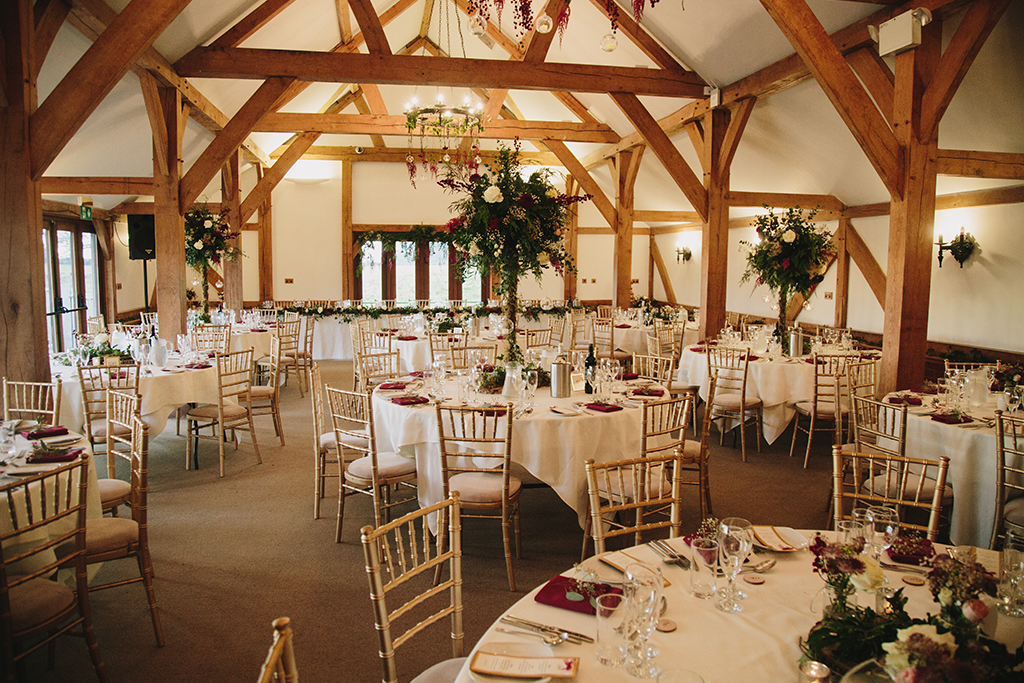 Tall displays of deep green foliage and burgundy and cream flowers adorned the tables at this barn wedding venue near Manchester
