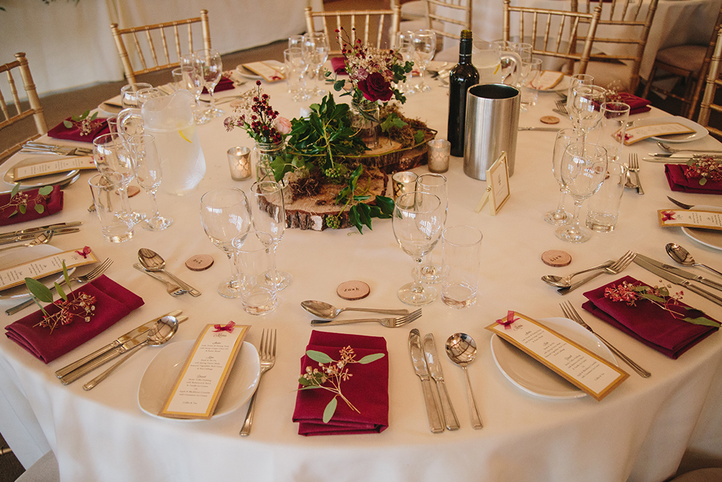 Round wedding tables were decorated with wood slices and pretty flowers with coordinating burgundy napkins at this rustic winter wedding at Sandhole Oak Barn
