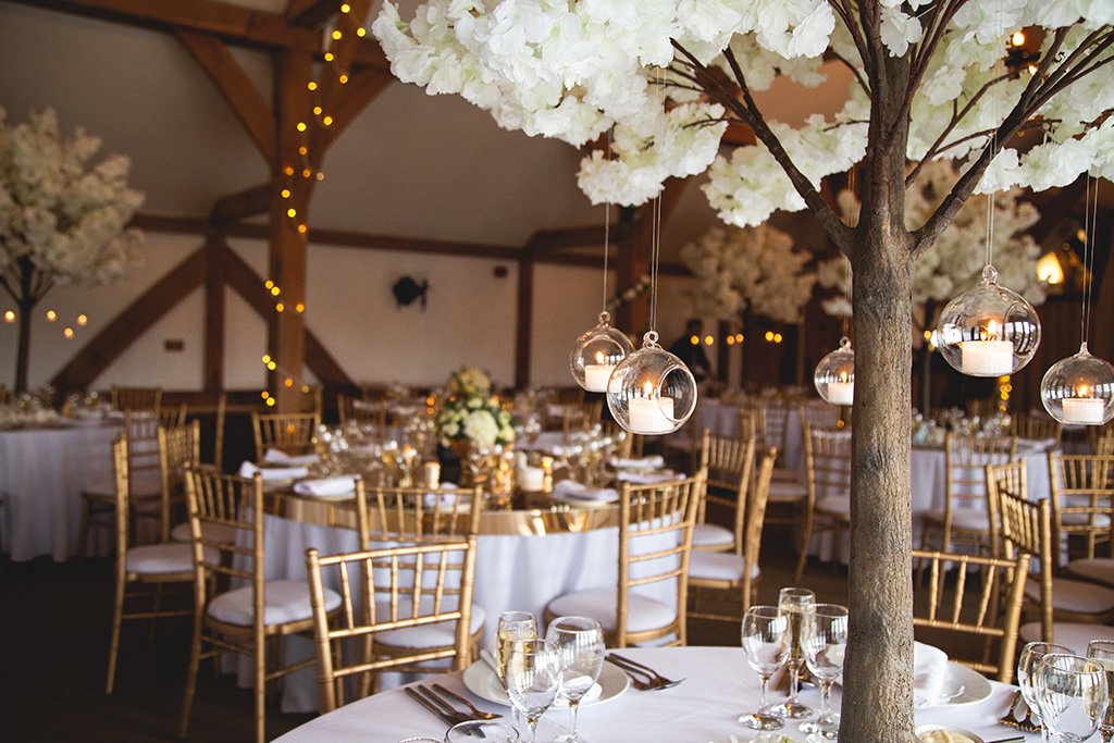 The tables were decorated with miniature blossom trees with hanging candles baubles at Sandhole Oak Barn in Cheshire