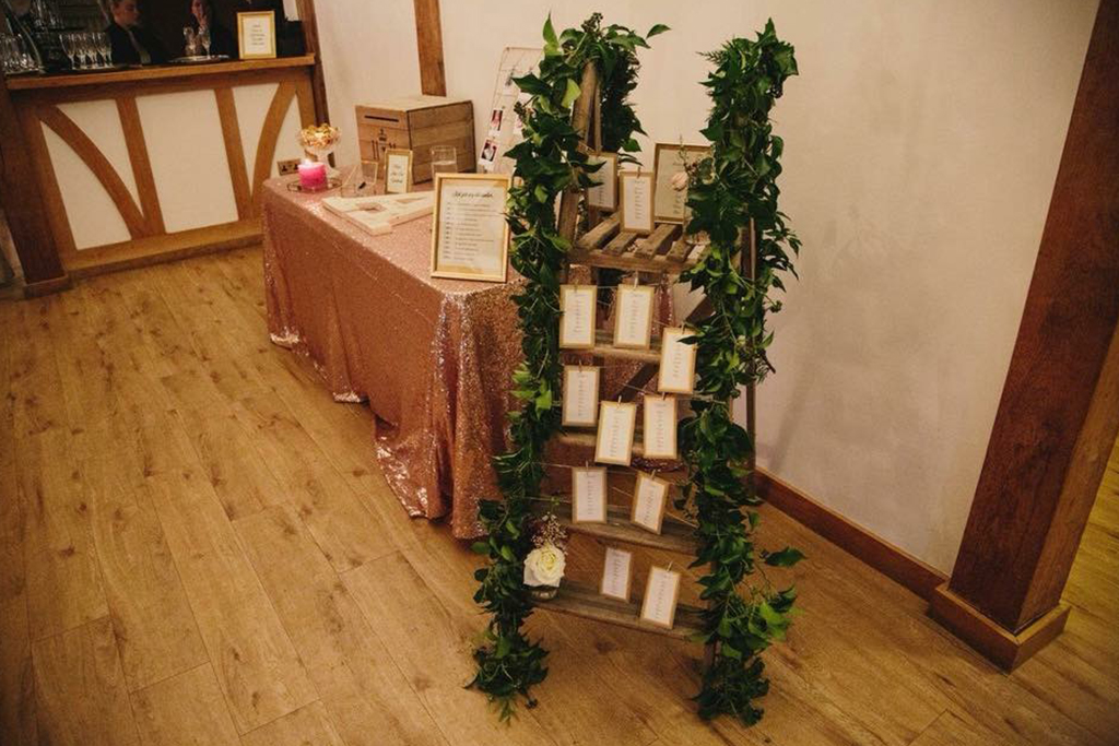 The couple chose a rustic wooden ladder shelf decorated with lush foliage to display their table plan at Sandhole Oak Barn