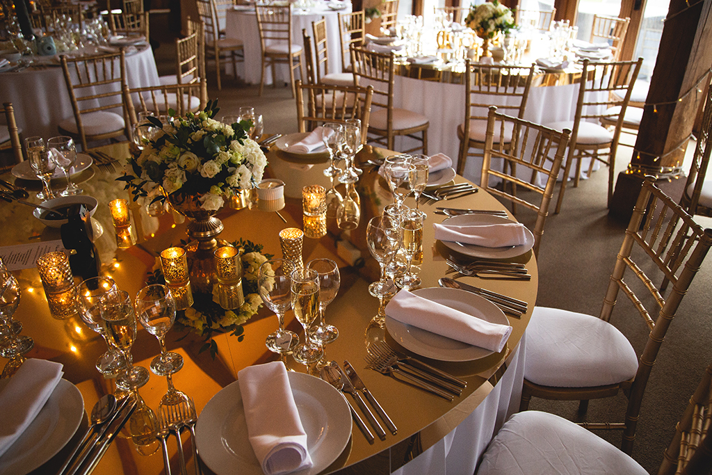 The tables were decorated with gold table-toppers and lots of pretty gold tealight holders at this spring wedding at Sandhole Oak Barn near Staffordshire