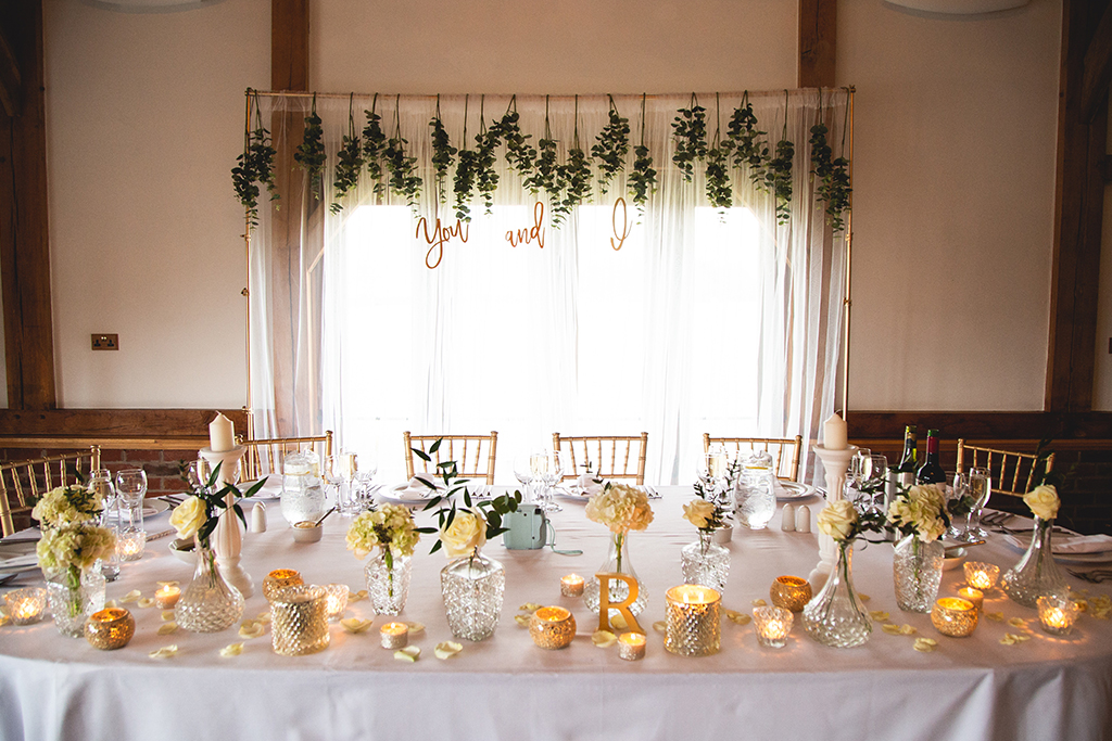 The top table was decorated with pretty vases of cream roses and gold tea light holders and a gold frame with hanging foliage was used as a backdrop at this spring wedding at Sandhole Oak Barn