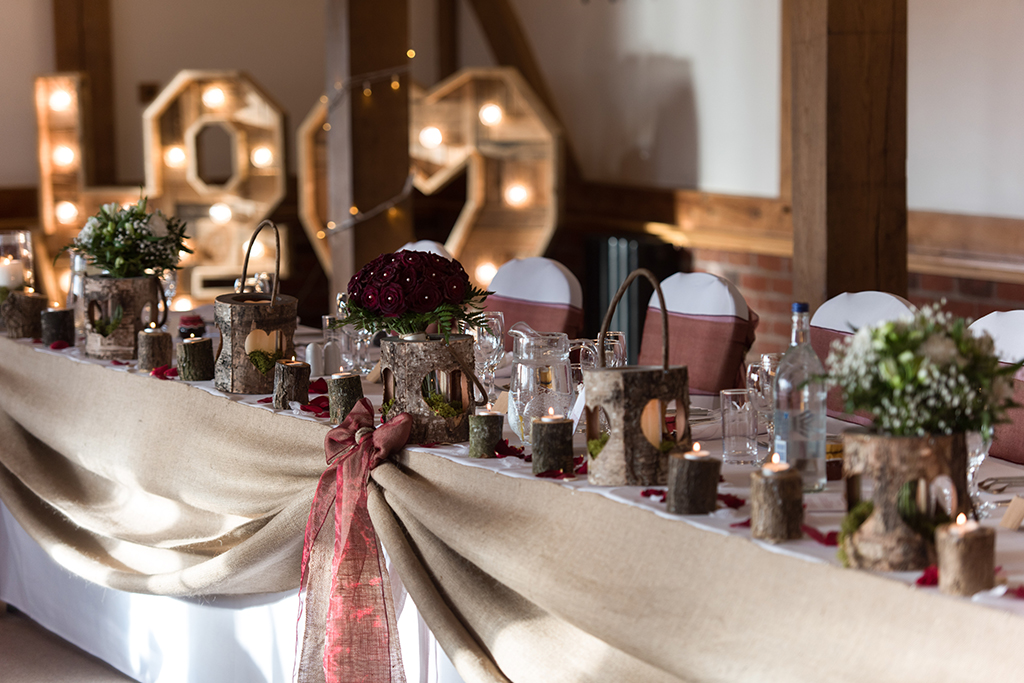 The top table was adorned with rustic wedding decorations at this winter wedding at Sandhole Oak Barn in Cheshire