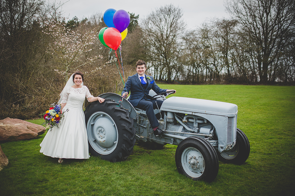 The happy newlyweds pose for a fun wedding photo on the tractor at Sandhole Oak Barn in Cheshire