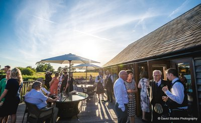 The guests enjoy mingling on the verandah on a summers evening at this North West wedding barn venue
