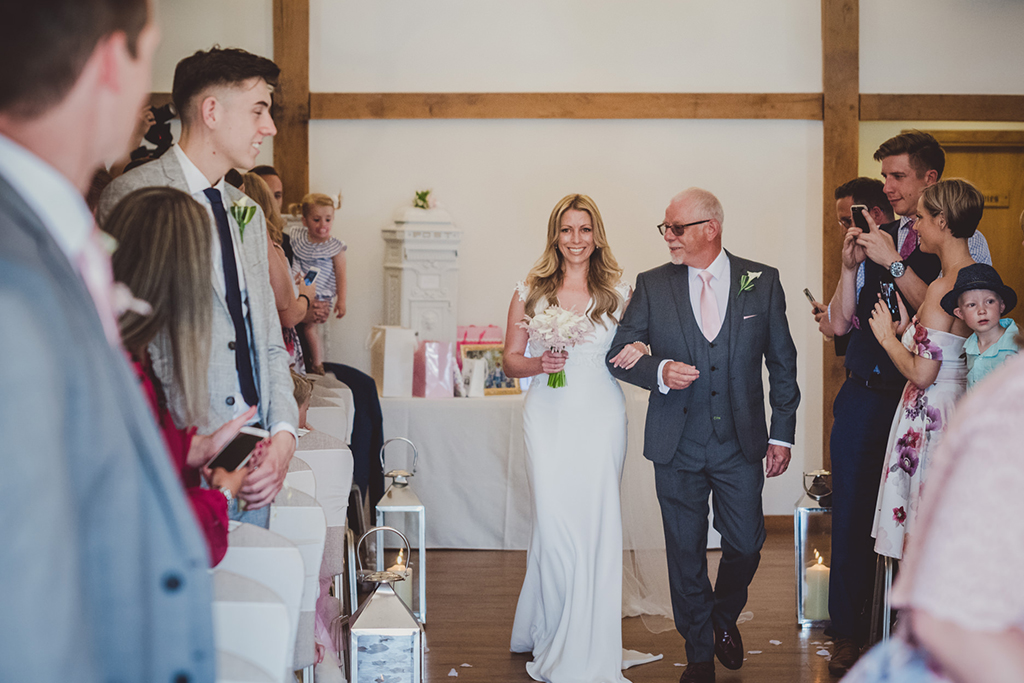 The happy bride-to-be and her father walk down the aisle at this North West barn wedding