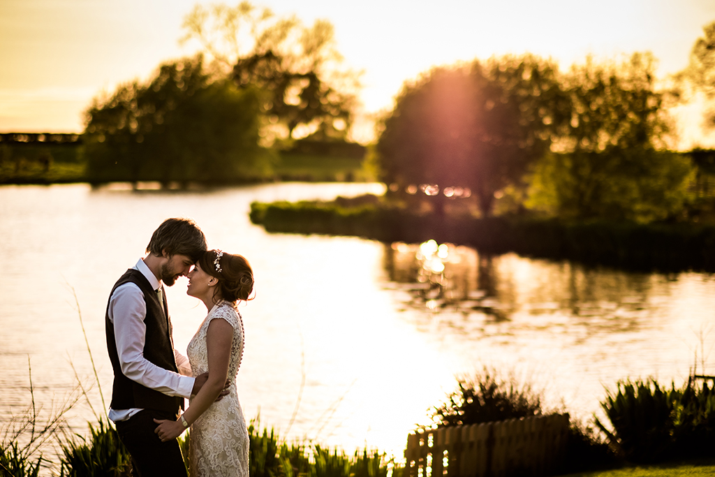The lake at sunset offers the most beautiful backdrop to your wedding photos at Sandhole Oak Barn in Cheshire