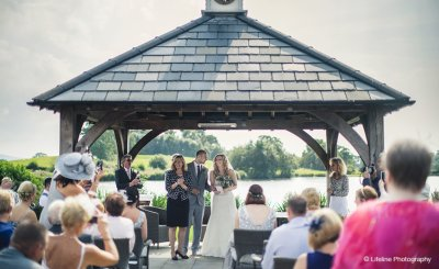 The wedding guests applaud the happy newlyweds at their outdoor wedding ceremony at Sandhole Oak Barn in Cheshire