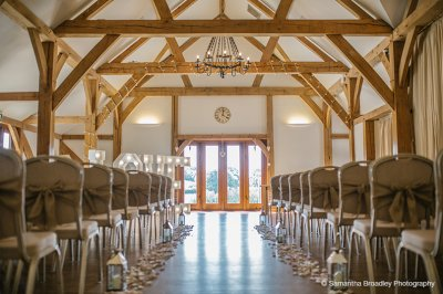 The wedding aisle in the Oak Barn was lined with lanterns and pretty petals ready for the wedding ceremony at Sandhole Oak Barn.