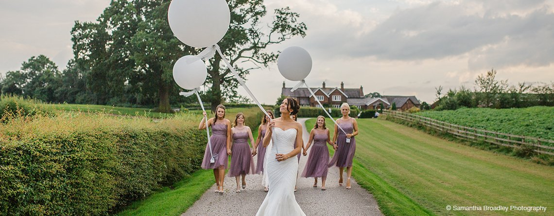 The bride and her bridesmaids pose for an outdoor wedding picture holding elegant white wedding balloons.