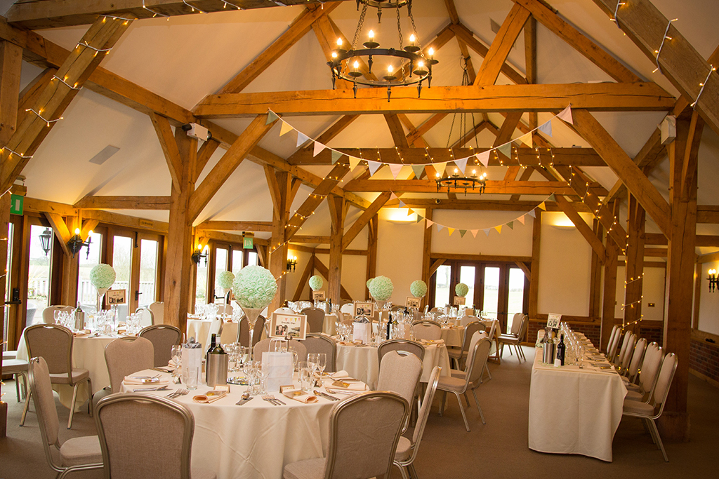 The oak barn decorated with pastel bunting and table decorations with fairy lights along the beams
