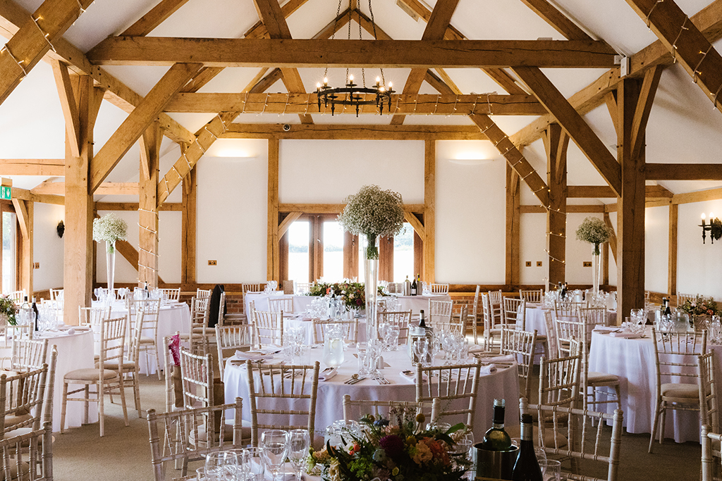 The oak barn was set up for the wedding breakfast with large arrangements pretty gypsophila as table centrepieces