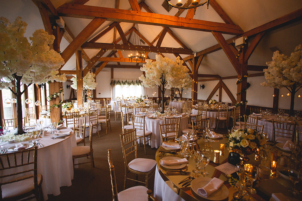 The Oak Barn looked beautiful with white blossom tree table centrepieces and tealights at this Spring wedding at Sandhole Oak Barn in Cheshire