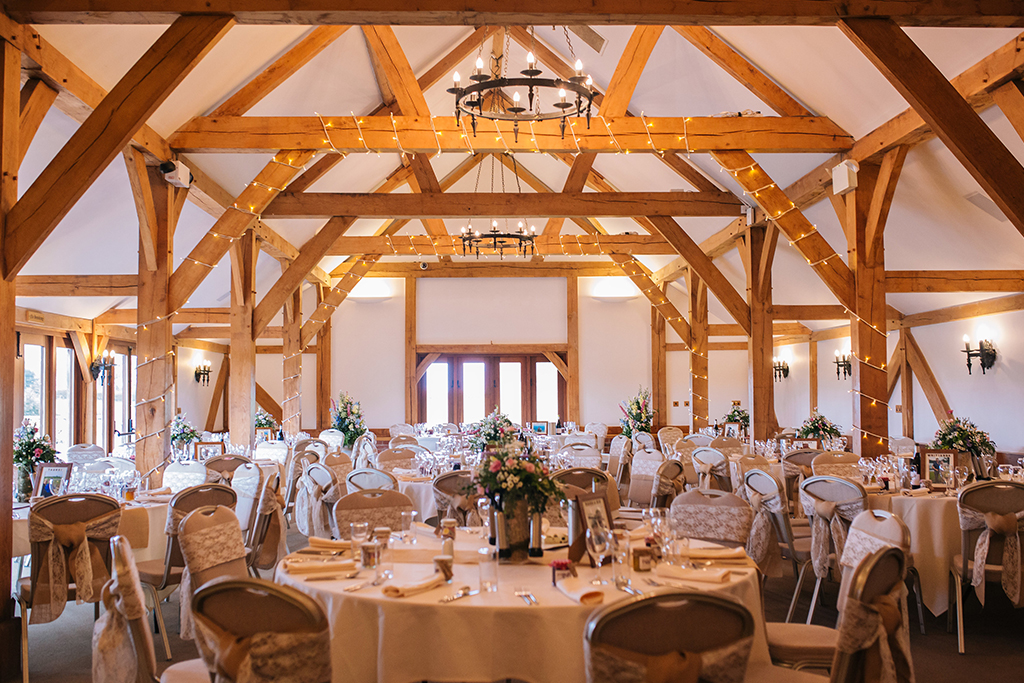 The Oak Barn has was set up for the wedding breakfast with fairy lights and pretty lace sashes on the chair