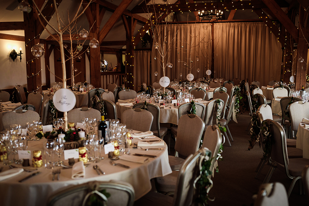 The barn at Sandhole Oak Barn was decorated with twinkly fairy lights and festive items at this winter wedding in Cheshire