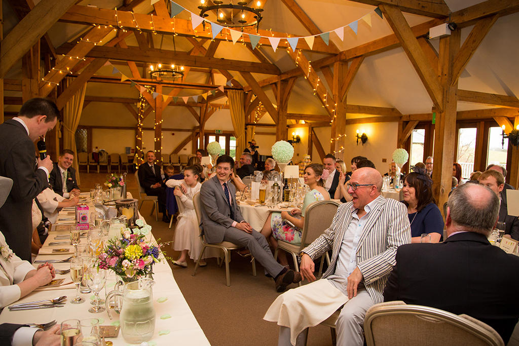The wedding guests enjoy listening to the groom's wedding speech at this barn venue in Cheshire