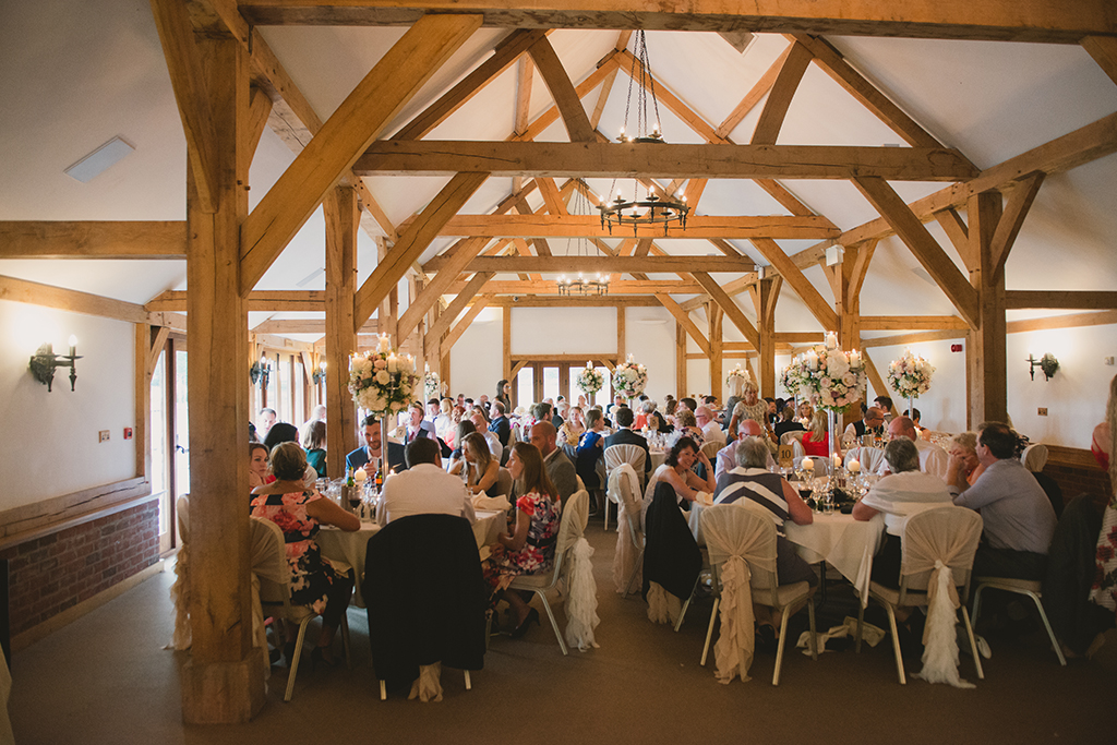Guests sit down in the stylish Oak Barn to enjoy a delicious wedding breakfast created by the exclusive wedding caterers
