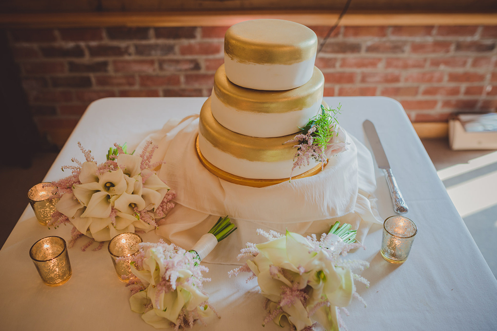 The bride chose a simple but elegant 3 tier wedding cake decorated with delicate flowers for her barn wedding at Sandhole Oak Barn.