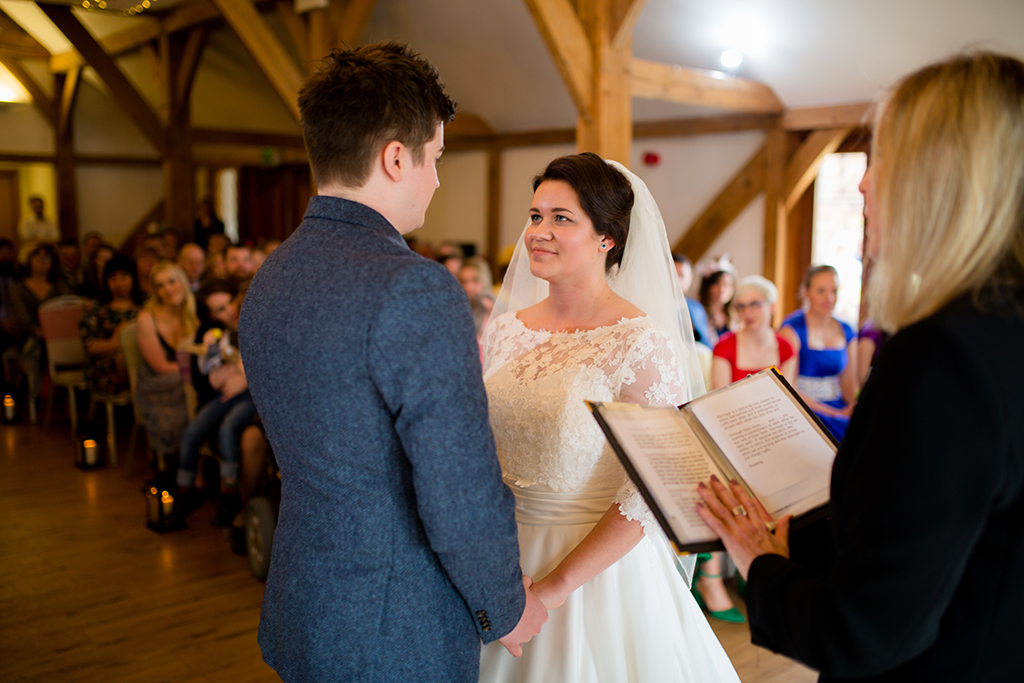 The bride and groom say their vows at their wedding ceremony at Sandhole Oak Barn in Cheshire