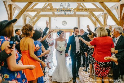 The happy couple are congratulated by their wedding guests after their wedding ceremony at Sandhole Oak Barn near Manchester