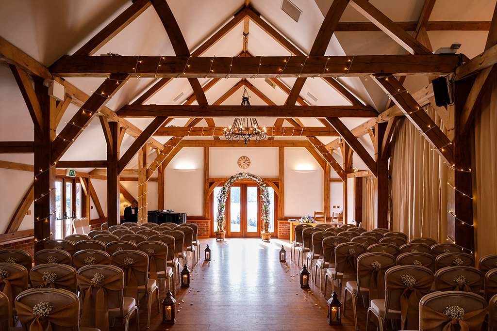 The rustic Oak Barn is set up for the wedding ceremony with fairy lights on the beams and pretty bunches of gypsophilia tied to chairs.