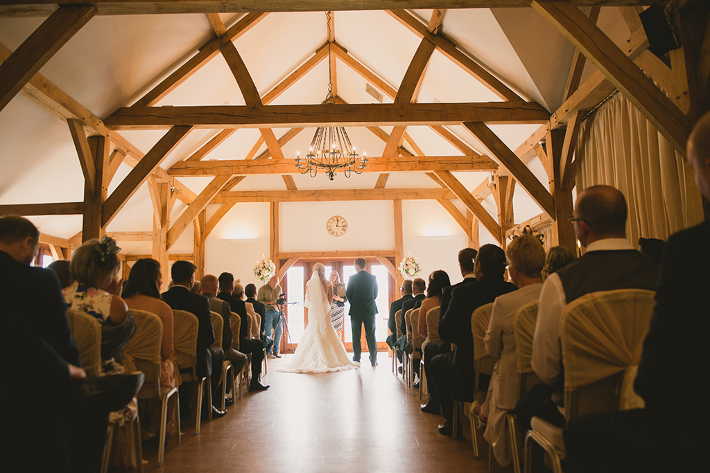 The bride and groom exchange wedding vows in the intimate and romantic Oak Barn