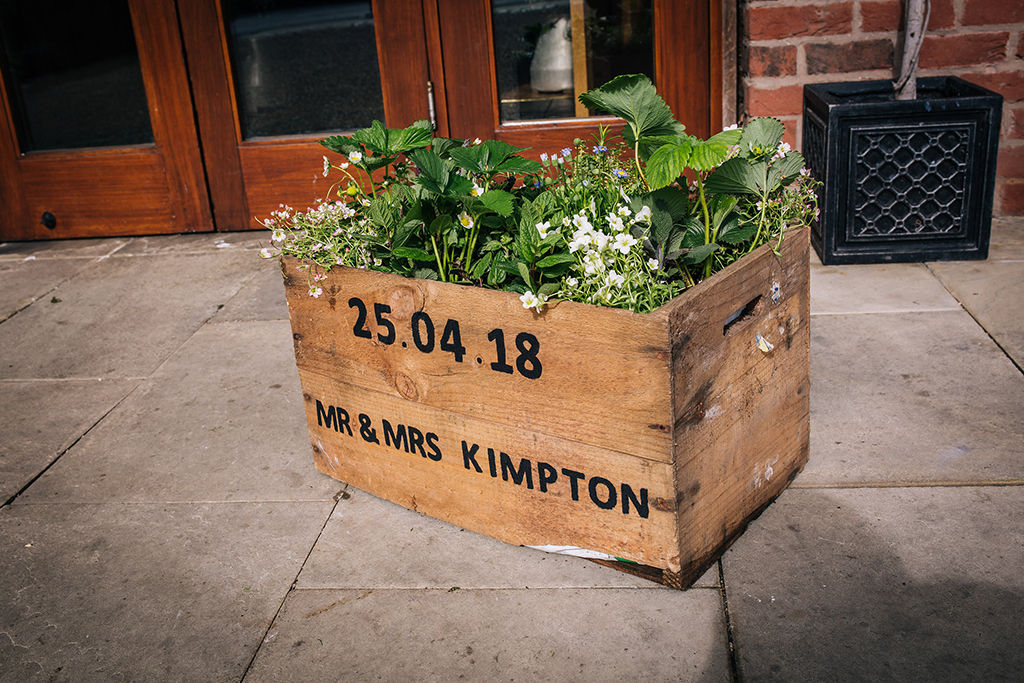 Spring wedding flowers and lush foliage were displayed in a personalised wedding crate at Sandhole Oak Barn