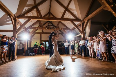 The happy couple enjoy their first dance as their wedding guests look on at this barn wedding venue near Manchester