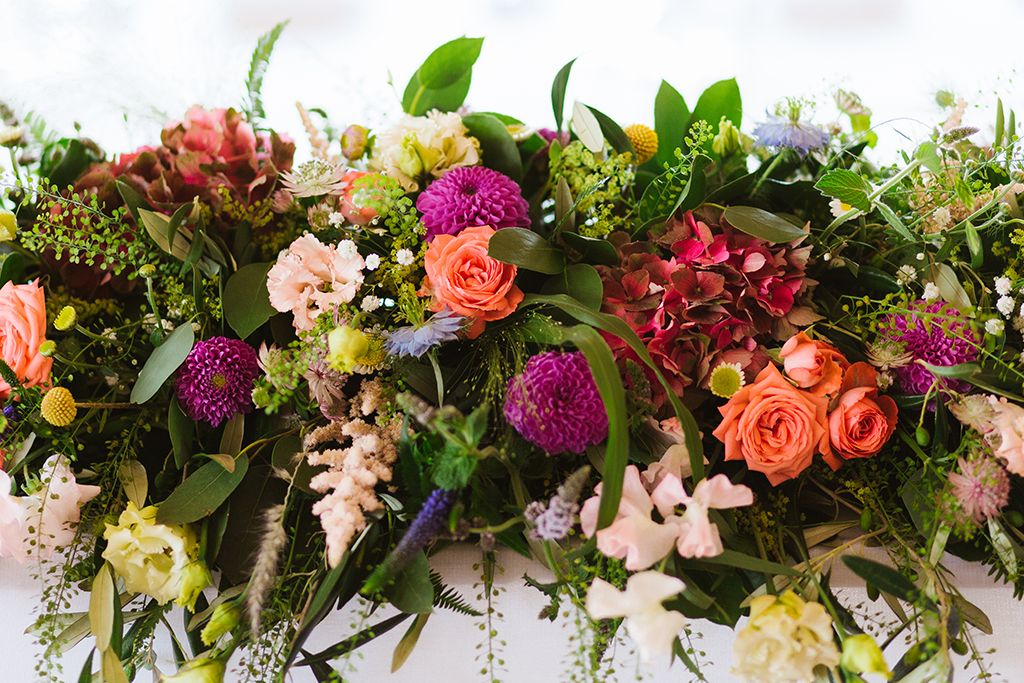 The wedding tables were decorated with beautiful colourful summer wedding flowers at this Cheshire barn wedding