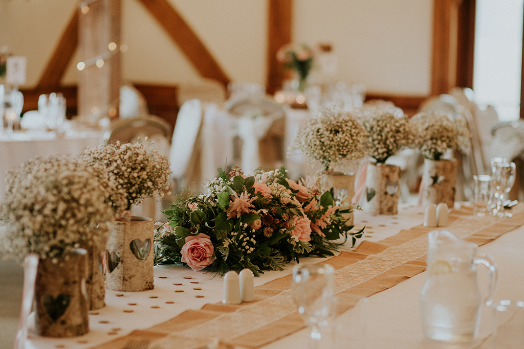 An abundance of pretty spring flowers were used to decorate the top table at this rustic wedding at Sandhole Oak Barn