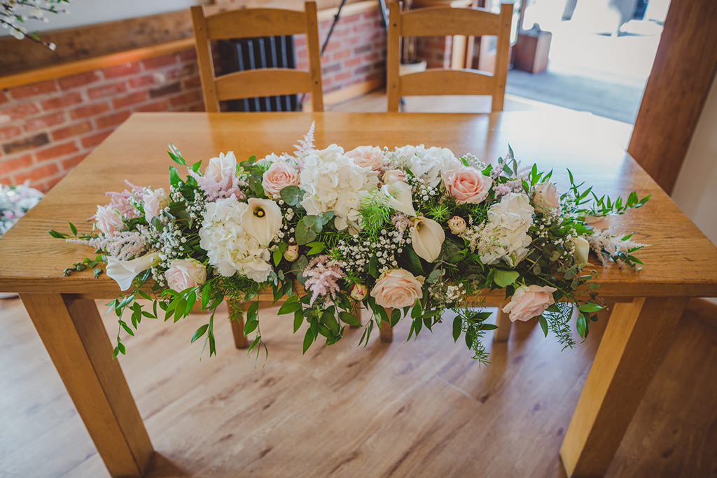 The ceremony table was decorated with an arrangement of delicate pale pink and white wedding flowers and lush green foliage