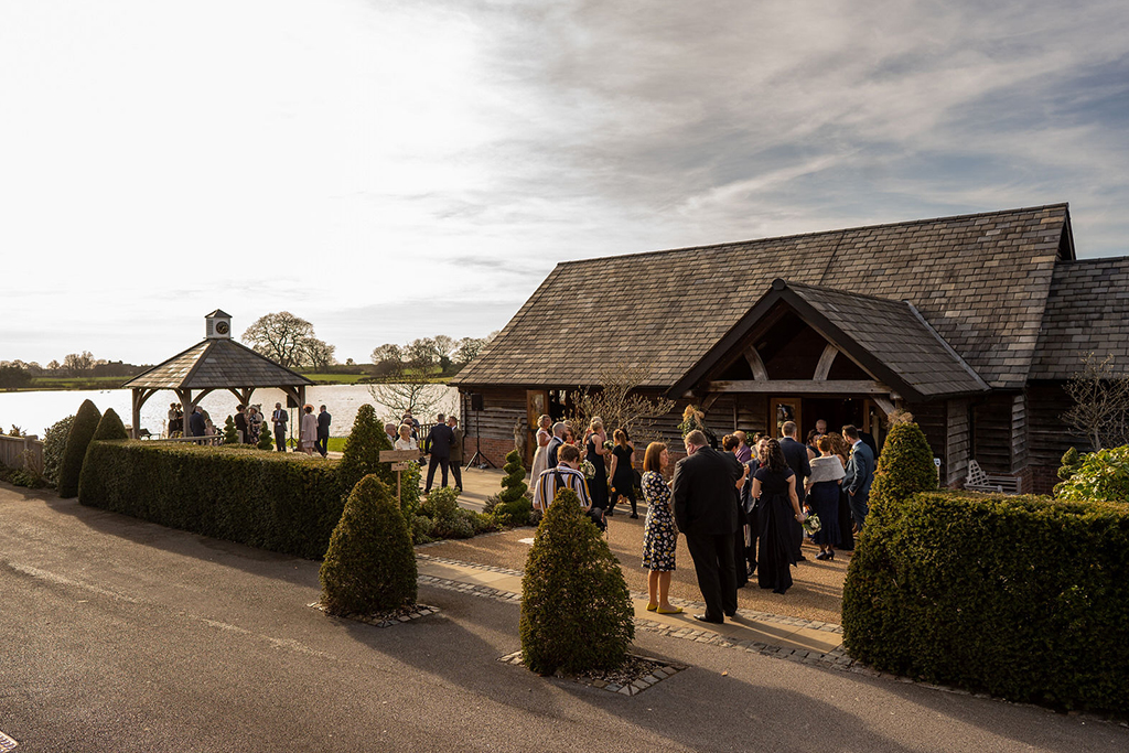 Wedding guests enjoy mingling in the winter sunshine at Sandhole Oak Barn