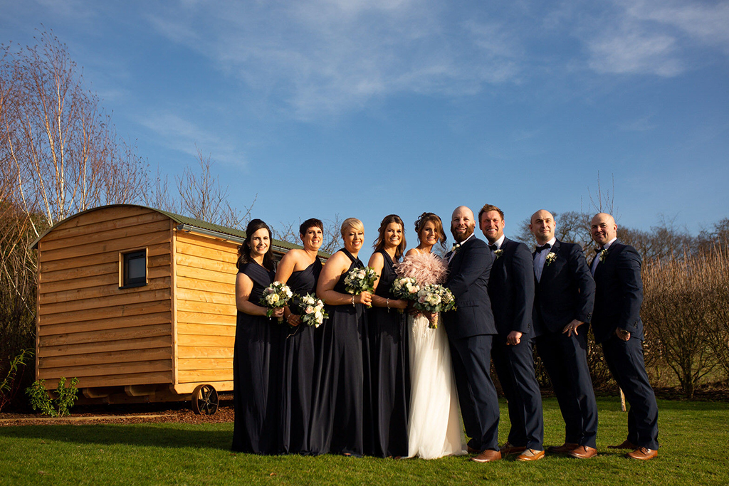The wedding party pose for a photo by the groom's hut preparation room at Sandhole Oak Barn