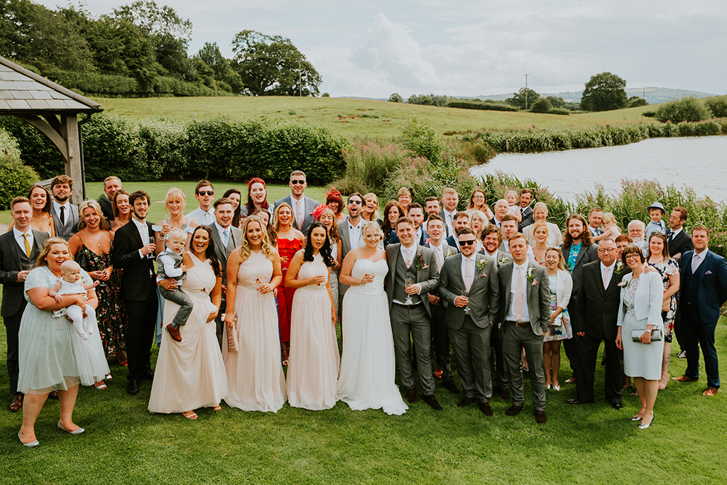 The bride and groom stand together with all their wedding guests on the lawns next to the lake